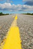 Närbild av landshuvudvägen med den gula linjen Royaltyfria Bilder