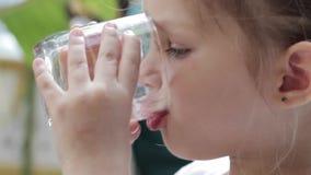 Närbild av lite den gulliga flickan som dricker rent vatten från ett exponeringsglas