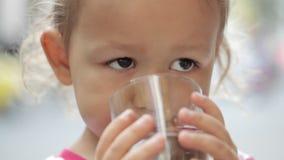 Närbild av lite den gulliga flickan som dricker rent vatten från ett exponeringsglas lager videofilmer
