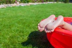 Närbild av lite flickas ben i pölen Royaltyfri Foto