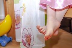 Närbild av liten flickafot, medan sitta på säng arkivbild