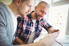 Närbild av lyckliga affärsmän som använder den digitala minnestavlan i idérikt kontor Arkivbild