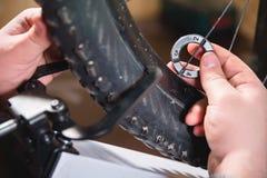Närbild av mäns händer med en specialiserad skiftnyckel på en ställning i seminariet som drar åt eker av hjulet arkivfoto