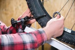 Närbild av mäns händer med en specialiserad skiftnyckel på en ställning i seminariet som drar åt eker av hjulet arkivbilder