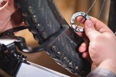 Närbild av mäns händer med en specialiserad skiftnyckel på en ställning i seminariet som drar åt eker av hjulet arkivfoton