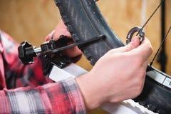 Närbild av mäns händer med en specialiserad skiftnyckel på en ställning i seminariet som drar åt eker av hjulet arkivbild