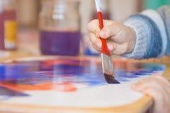 Närbild av målarfärger med målarpenseln och teckningen för liten hand för unge` s den hållande Arkivbild