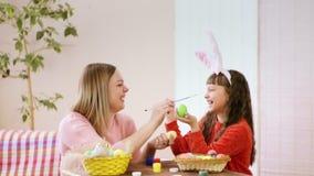 Närbild av mamman och dotter, som dekorerar testiklar och trycker sig på med borstar, och skratt lyckliga easter arkivfilmer