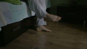 Närbild av manfot som får ut ur säng lager videofilmer