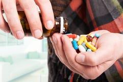 Närbild av manhanden mycket av preventivpillerar arkivfoto