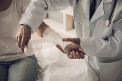 Närbild av manlig doktor Bandaging Female Hand fotografering för bildbyråer