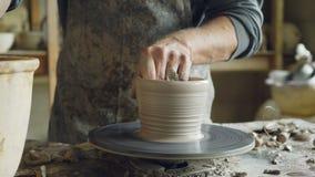 Närbild av manliga händer som dekorerar denfärdiga keramiska krukan på snurrkeramiker` s som kastar hjulet som gör prydnaden lager videofilmer