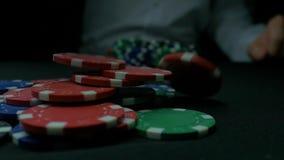 Närbild av mannen som kastar chiper för en poker i ultrarapid Närbilden av handen med att kasta dobbleri gå i flisor på svart bak lager videofilmer
