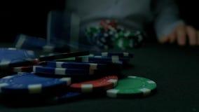 Närbild av mannen som kastar chiper för en poker i ultrarapid Närbilden av handen med att kasta dobbleri gå i flisor på svart bak arkivfilmer
