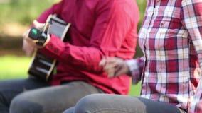 Närbild av mannen som spelar låsande fast fingrar för gitarr och för kvinna arkivfilmer