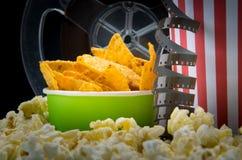 Närbild av mellanmål på biostången, med videoband och en hink av nachos royaltyfri foto
