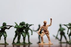 Närbild av miniatyren per gruppen av plast- leksaksoldater på kriget royaltyfri bild