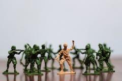 Närbild av miniatyren per gruppen av plast- leksaksoldater på kriget arkivfoto