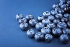Närbild av mogna och ljusa blåbär, på mörkret - blå bakgrund Nya, saftiga sunda bär som är fulla av vitaminer arkivbild