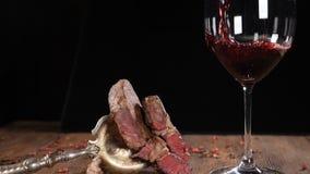 Närbild av ny lagad mat biff som ligger på träbrunt bräde Rött vin som häller i ultrarapid Kött på tappninggaffel HD lager videofilmer