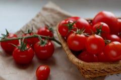 Närbild av nya körsbärsröda tomater i en vide- korg på vit bakgrund, selektiv fokus Arkivfoton