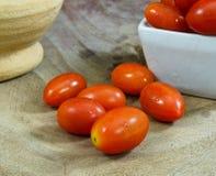 Närbild av nya mogna körsbärsröda tomater på trä Arkivbilder