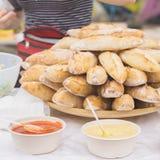 Närbild av nya varma bagetter och olika såser för smörgåsar, selektiv fokus Händer av säljaren i bakgrund med Arkivbilder