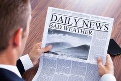 Närbild av nyheterna för affärsmanläsningväder Royaltyfria Foton