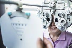 Närbild av optometrikern som gör en ögonexamen på ung kvinna arkivfoton
