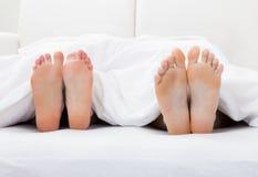 Närbild av pars fot som sover på säng Fotografering för Bildbyråer
