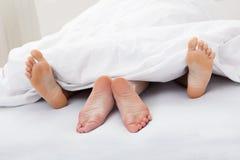 Närbild av pars fot som sover på säng Royaltyfria Foton