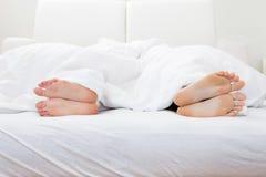Närbild av pars fot som sover på säng Arkivbilder