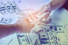 Närbild av Person Hand Giving Money To annan hand arkivfoto