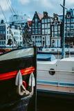 Närbild av pilbågeframdelen av det träskeppet och ankaret Amsterdam Nederländerna som dansar hus över floden Amstel i royaltyfri foto