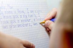 Närbild av pojkehanden med blyertspennan som skriver engelska ord vid handen på traditionellt vitt notepadpapper royaltyfria foton