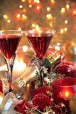 Närbild av rött vin i exponeringsglas, stearinljus och baubles Royaltyfri Bild