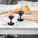 Närbild av rött vin, vitt bröd och olika typer av den nya korven, mortadella på picknicken, parti för prydnadpapper för bakgrund  Arkivfoto
