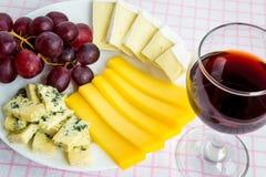 Närbild av rött vinexponeringsglas och den vita plattan med trädsorter av skivad ost och söta röda druvor Ostar som täckas med ät royaltyfri bild
