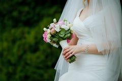 Närbild av rosor som in gifta sig buketten i händer av en slank brud Royaltyfria Bilder