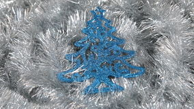 Närbild av rotationen av en blå julgran som ligger på ett silverglitter Jul bakgrund, glitter arkivfilmer