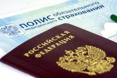 Närbild av rysk sjukförsäkringpolitik och rysspass och några preventivpillerar royaltyfria foton