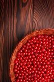 Närbild av saftiga röda vinbär på en brun bakgrund En korg som fylls med den smakliga vinbäret Näringsrika organiska bär Arkivbild