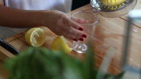 Närbild av sammanpressning av citronen och att hälla citronjuice in i exponeringsglas arkivfilmer