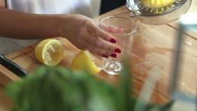 Närbild av sammanpressning av citronen och att hälla citronjuice in i exponeringsglas lager videofilmer