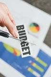 Närbild av sax som klipper ordet & x22en; budget& x22; ovanför finansiella rapporter och diagram Royaltyfri Foto