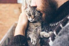Närbild av skäggmannen i den isländska tröjan som är hållande och kyssa hans gulliga katt för spinna Devon Rex Royaltyfri Foto