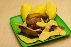 Närbild av skalade potatisar på en platta med en mjuk bakgrund arkivfoton