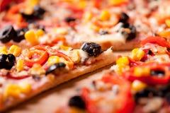 Närbild av skivan av matställepizza med skinka, oliv, mozzarella Arkivbild
