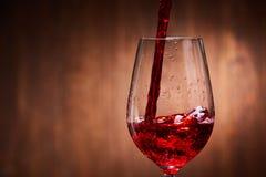 Närbild av smakligt rött vin som häller i det rena bräckliga vinglasanseendet mot träbakgrund Royaltyfria Foton