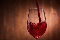 Närbild av smakligt rött vin som häller i det rena bräckliga vinglasanseendet mot träbakgrund Royaltyfri Fotografi